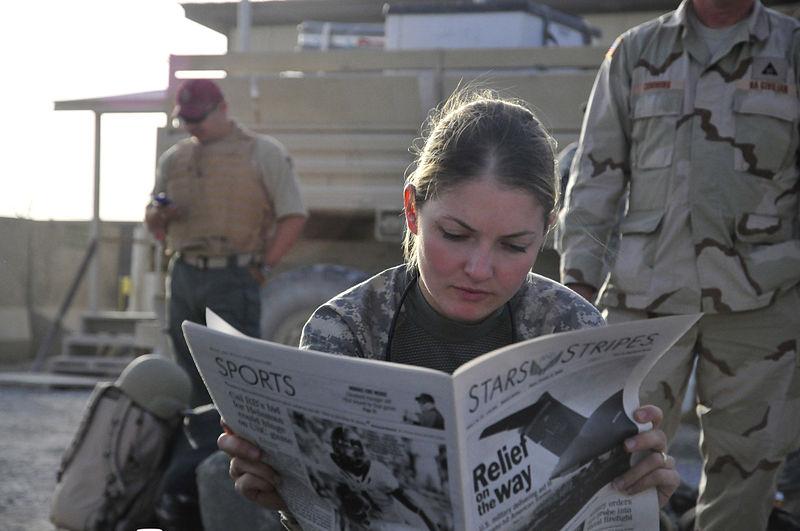 Mulher lendo jornal.