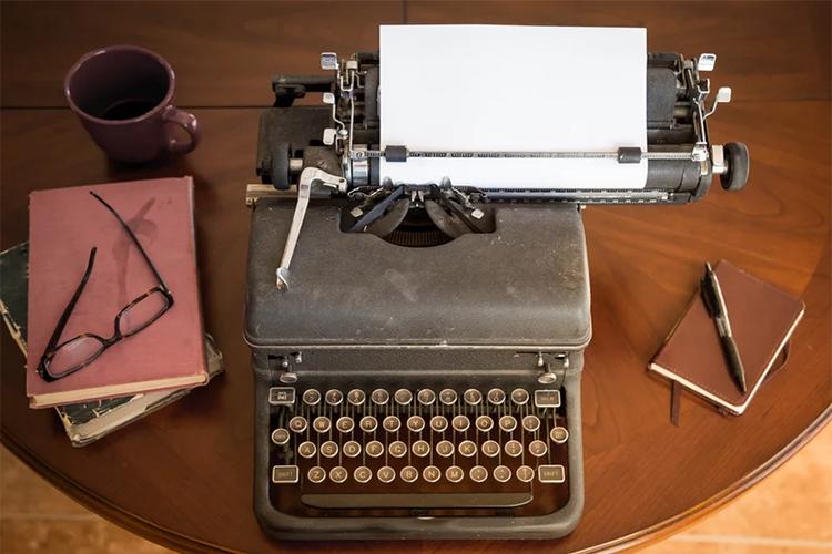 Máquina de escrever antiga no centro de uma mesa redonda. Ao seu lado se encontram uma caderneta de anotações com uma caneta e do outro lado alguns livros, um óculos de leitura e uma caneca.